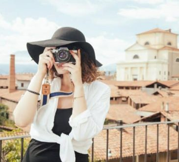 A woman wearing a hat and holding camera