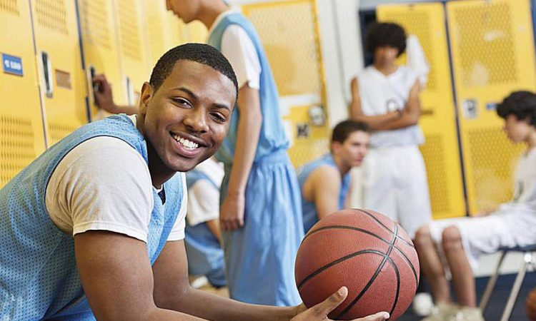 A person sitting on bunch and holding basketball game